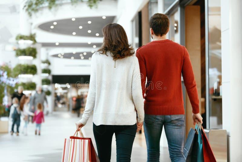 Compras Vista trasera de pares con los bolsos en centro comercial imagenes de archivo