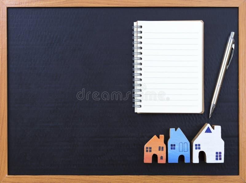 Compratore domestico, taccuino in bianco e casa miniatura di legno immagini stock