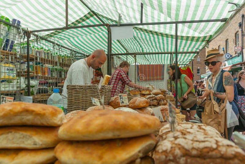Compratori e vedors nella stalla del mercato del forno nel mercato orientale di fine settimana di Londra fotografia stock libera da diritti
