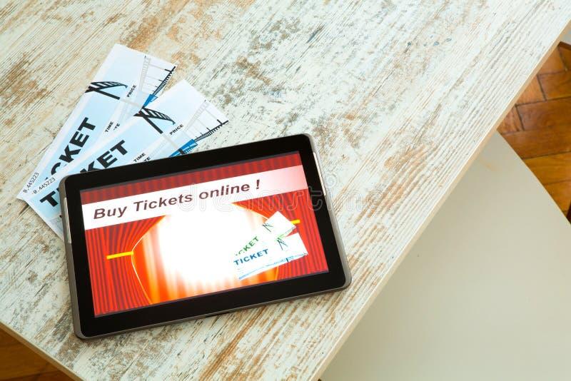 Compre boletos del cine en línea con un Tablet PC imagen de archivo