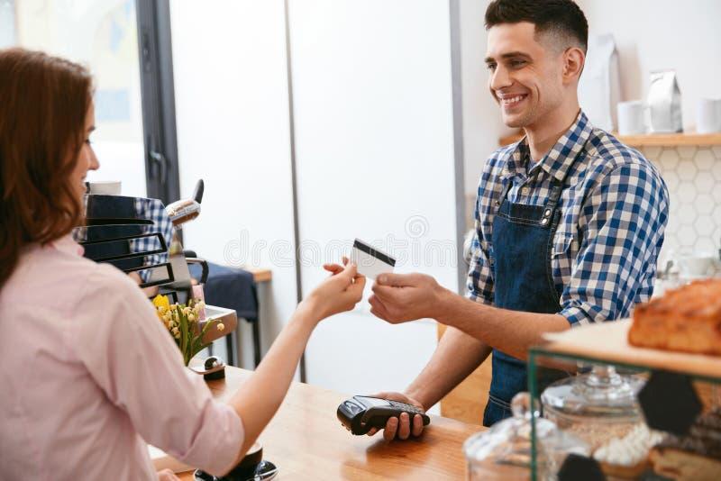 Compre o café Mulher que paga com o cartão de crédito no café fotografia de stock royalty free