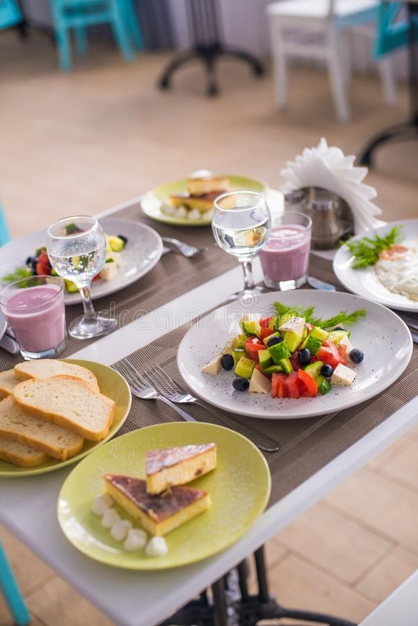A comprehensive breakfast of scrambled eggs with sausages, Greek salad and cheesecake. As well as yogurt royalty free stock photography