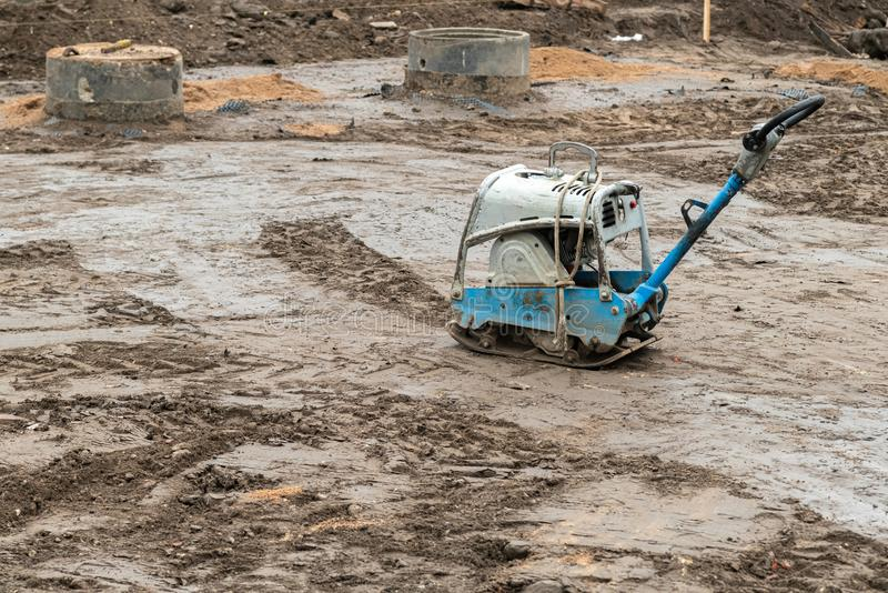 Compresor de la placa en la tierra en el emplazamiento de la obra Herramienta eléctrica vibratoria del martillo, tierra de compre fotos de archivo libres de regalías