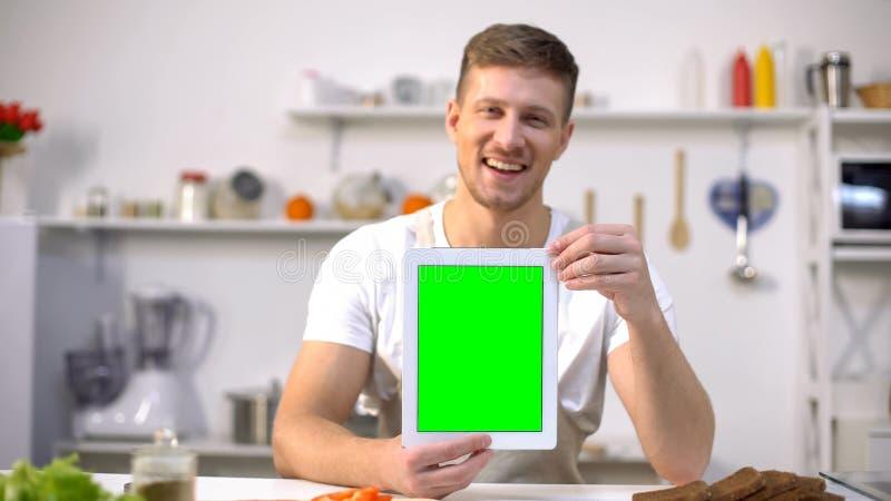 Compressa bella della tenuta dell'uomo con lo schermo verde, cucinante applicazione di corsi immagine stock libera da diritti