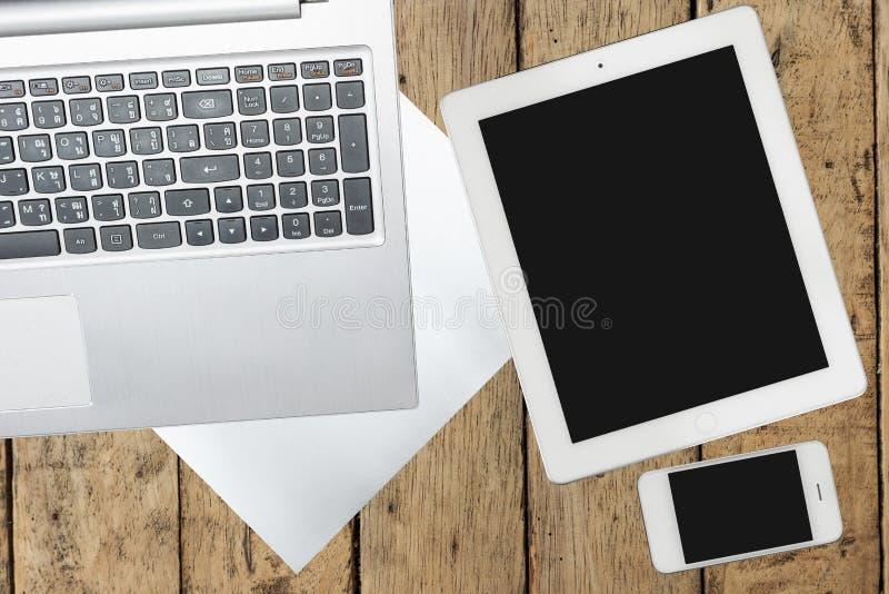 Compressa, computer, smartphone e carta sulla tavola di legno immagini stock