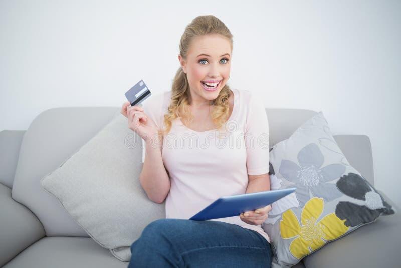 Compressa della tenuta e carta di credito bionde emozionanti casuali fotografia stock