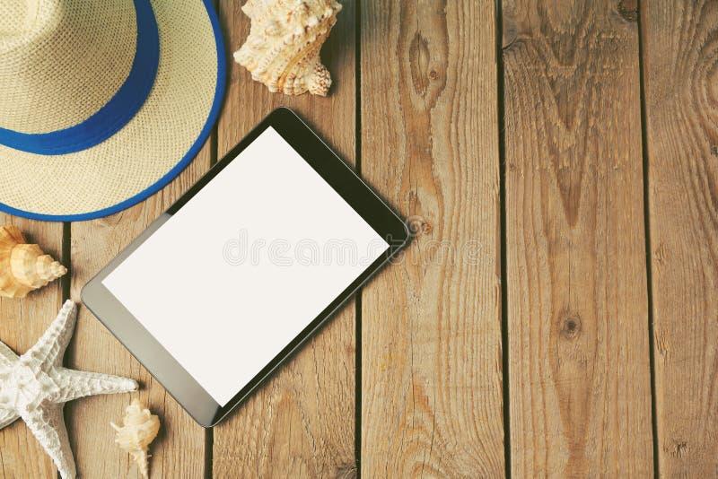 Compressa di Digital, cappello di estate e conchiglie su fondo di legno fotografie stock libere da diritti
