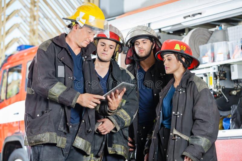 Compressa di Team Of Firefighters Using Digital immagini stock libere da diritti