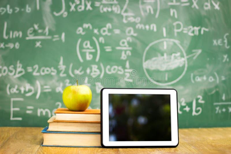 Compressa e mela di Digital sulla pila di libri immagine stock