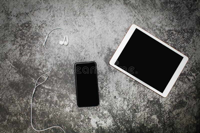 Compressa e smartphone di vista superiore su un vecchio lerciume grigio con headph immagine stock
