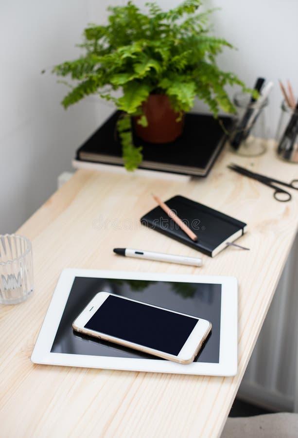 Compressa e smartphone sulla tavola di funzionamento fotografia stock