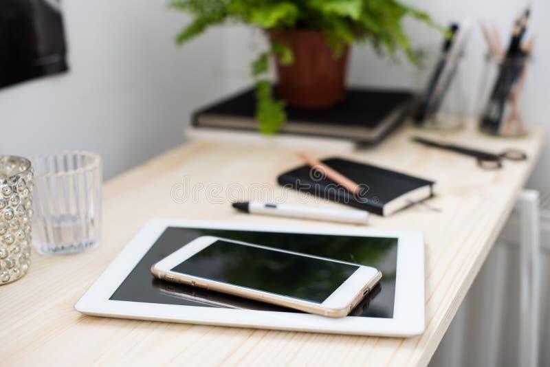 Compressa e smartphone sulla tavola di funzionamento fotografia stock libera da diritti