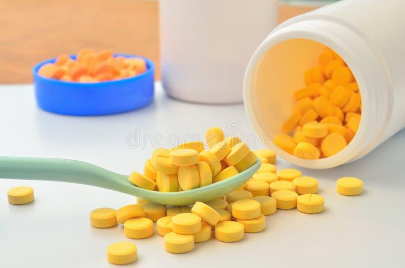 Compressa gialla della medicina sul cucchiaio e sulla bottiglia aperta di medicina immagini stock libere da diritti