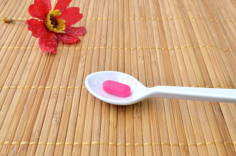 Compressa rosa della medicina sul cucchiaio e sul fiore rosso fotografia stock