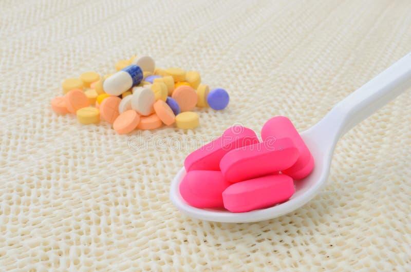 Compressa rosa della medicina sul cucchiaio e sul gruppo di compressa variopinta della medicina fotografie stock