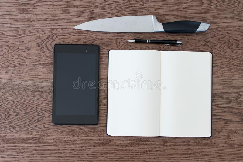 Compressa, taccuino, penna e un coltello su una tavola di legno Violenza AG immagini stock libere da diritti