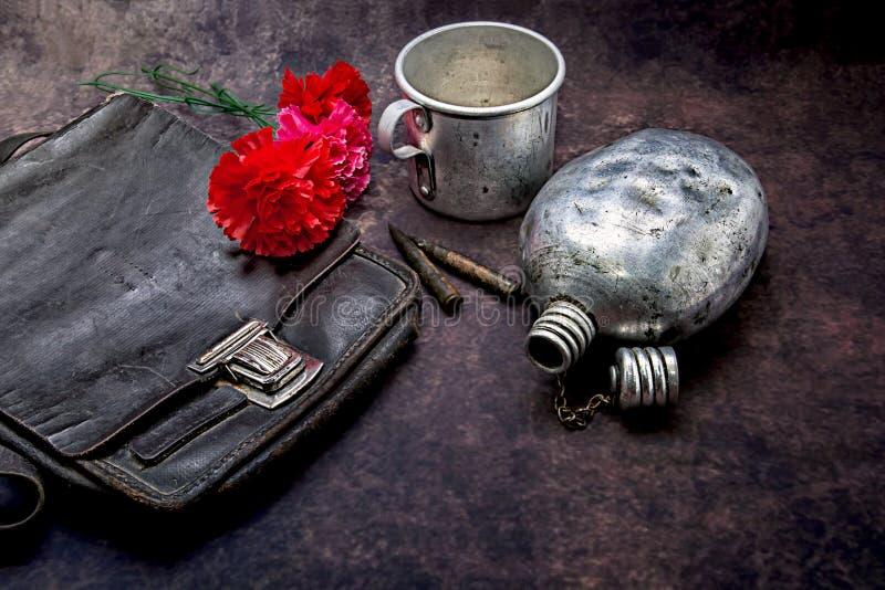 Compressa, tazza, boccetta, pallottole e garofani su un fondo scuro fotografia stock libera da diritti