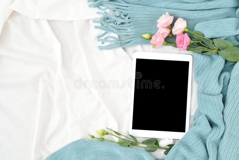 Compressa, telefono, tazza di caffè e fiori piani di disposizione sulla coperta bianca con il plaid del turchese fotografia stock
