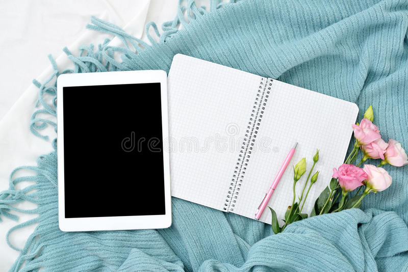 Compressa, telefono, tazza di caffè e fiori piani di disposizione sulla coperta bianca con il plaid del turchese fotografie stock