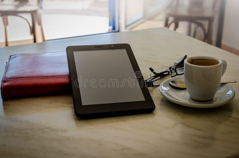Compressa, vetri, ordine del giorno e caffè sulla tavola fotografie stock libere da diritti