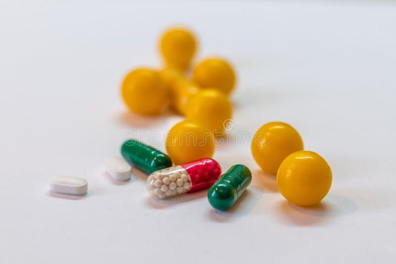 Compresse e capsule su un fondo bianco, assortimento variopinto delle compresse farmaceutiche della medicina immagine stock