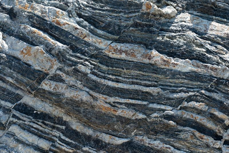 Compressed rock layers formation in various colors and thicknesses, on south central coast of the Mediterranean islan stock images