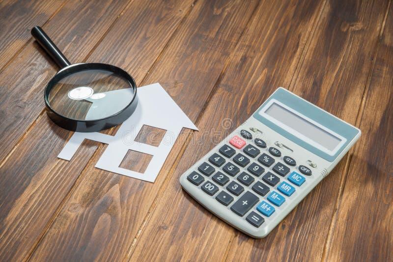Compri i calcoli di ipoteca della casa, calcolatore con la lente immagine stock libera da diritti