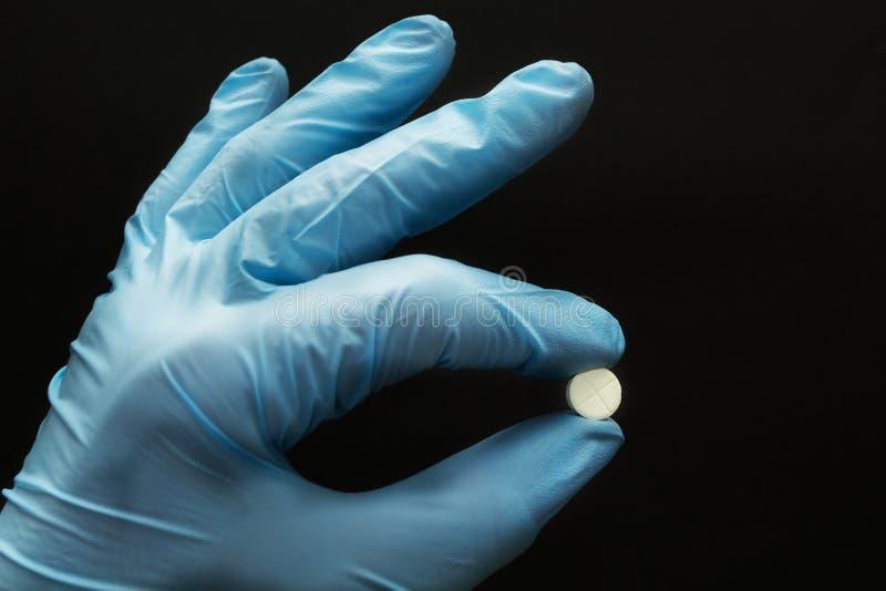 Comprimé blanc dans une main dans un gant bleu sur un fond noir, concept images stock