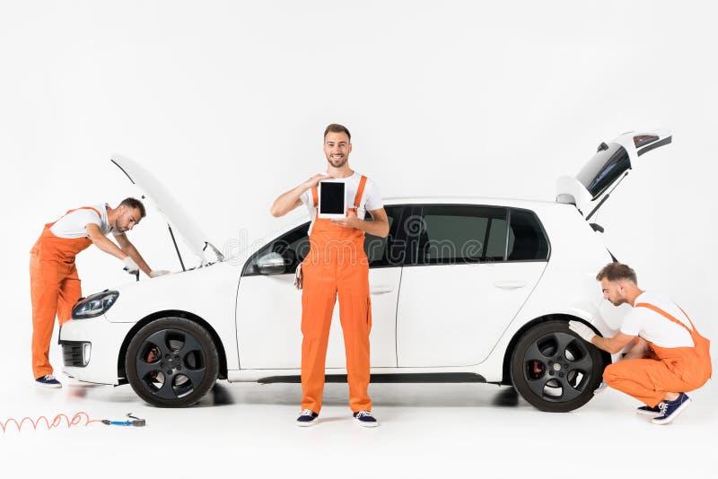 comprimé changeant d'apparence de pneu de voiture de mécanicien automobile et regard dans le capot ouvert de voiture image stock