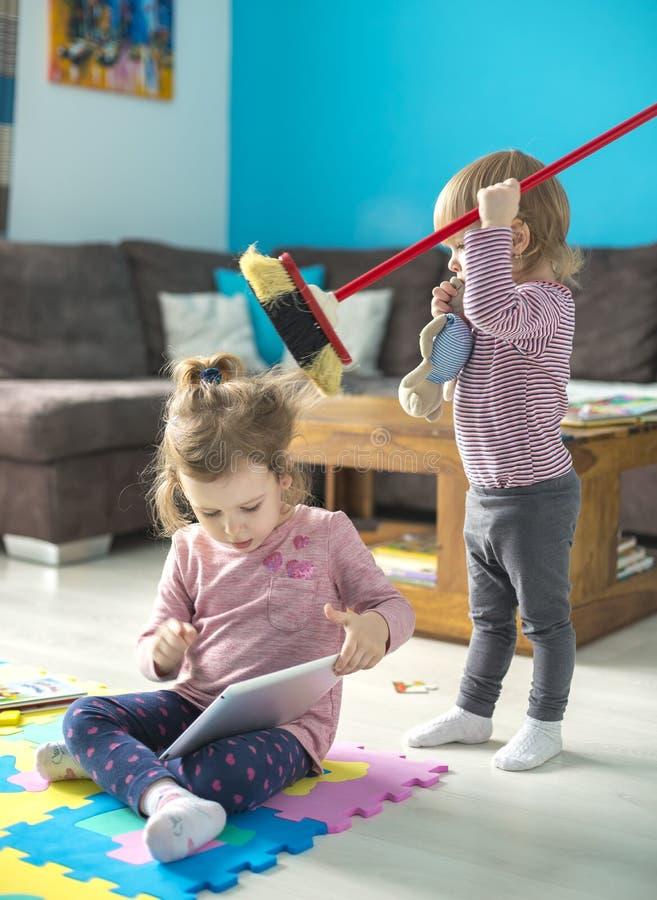 Comprimé d'utilisation de deux petites soeurs à la maison image libre de droits