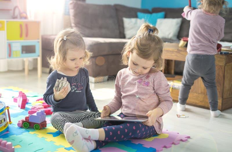 Comprimé d'utilisation de deux petites soeurs à la maison photographie stock libre de droits
