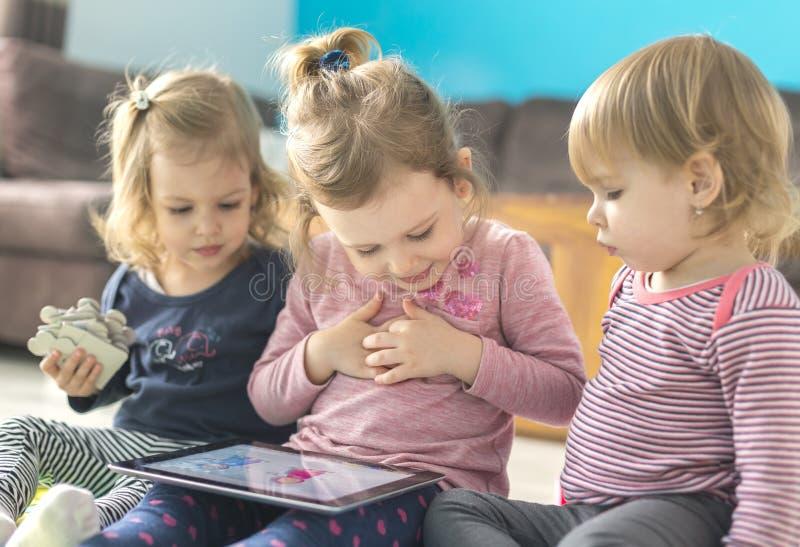 Comprimé d'utilisation de trois petites soeurs à la maison images libres de droits