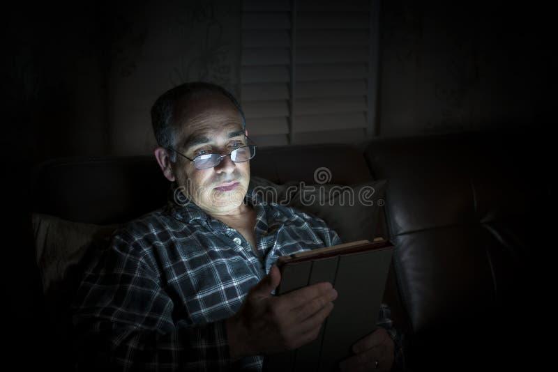 Comprimé de lecture d'homme la nuit photos stock