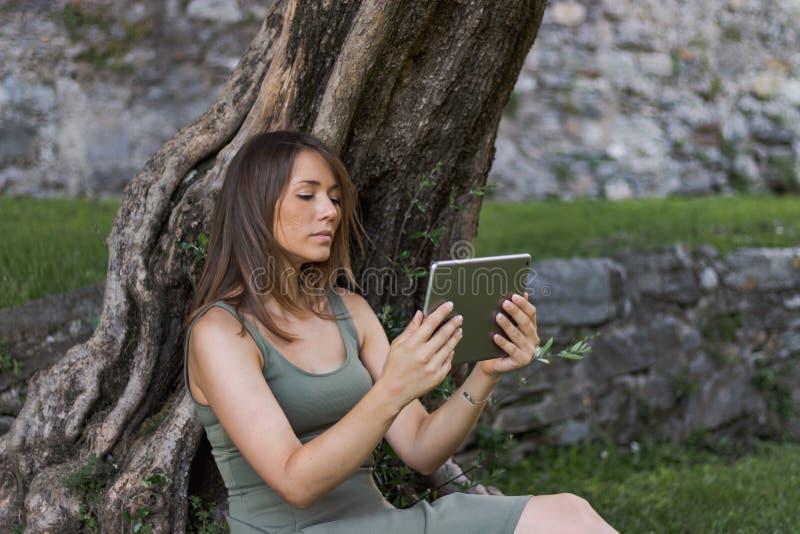 Comprimé de lecture de femme et apprécier le repos en parc sous l'arbre images libres de droits