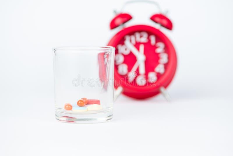 Comprimé de médecine, distribuant l'horloge en verre et rouge images libres de droits