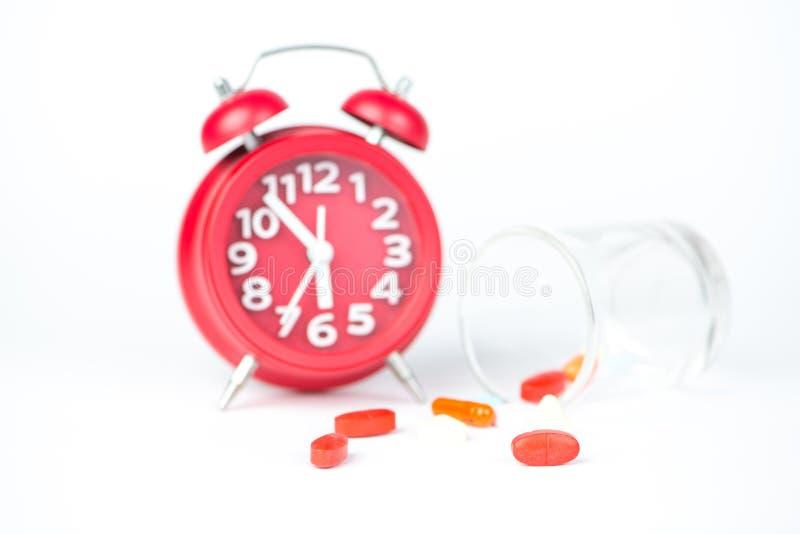 Comprimé de médecine, distribuant l'horloge en verre et rouge photo libre de droits
