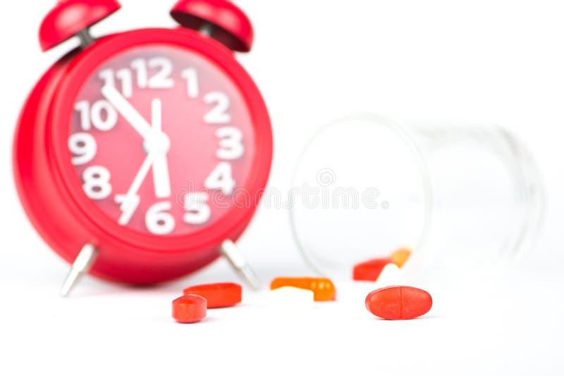 Comprimé de médecine, distribuant l'horloge en verre et rouge photographie stock