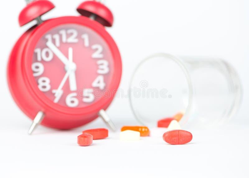 Comprimé de médecine, distribuant le Ti en verre et rouge de médecine d'exposition d'horloge photos stock