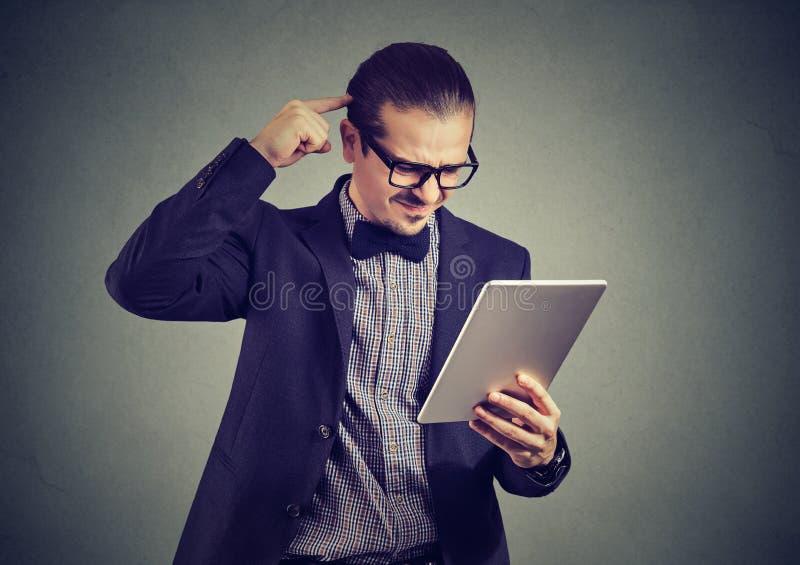 Comprimé de observation d'homme confus sur le gris photo stock