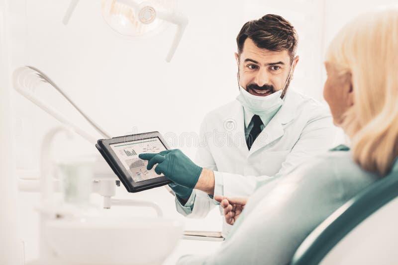 Comprimé de participation de dentiste et parler avec le patient photographie stock