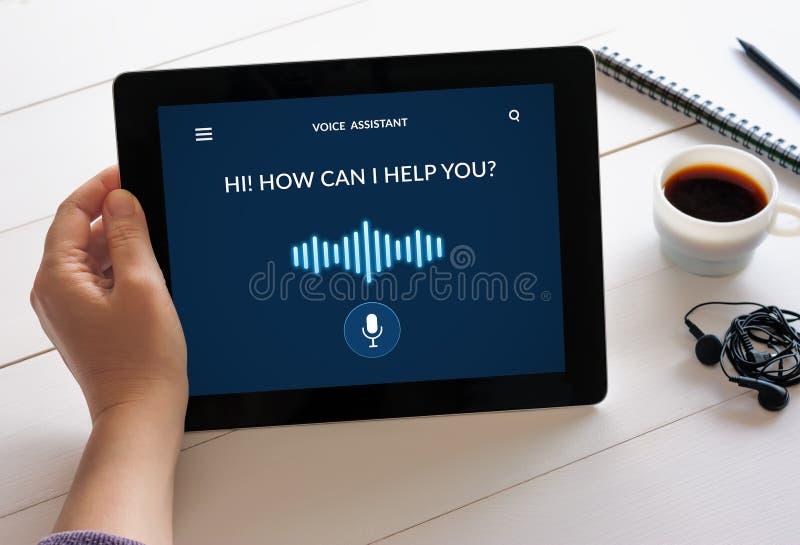 Comprimé de participation de main avec le concept auxiliaire de voix sur l'écran photos stock