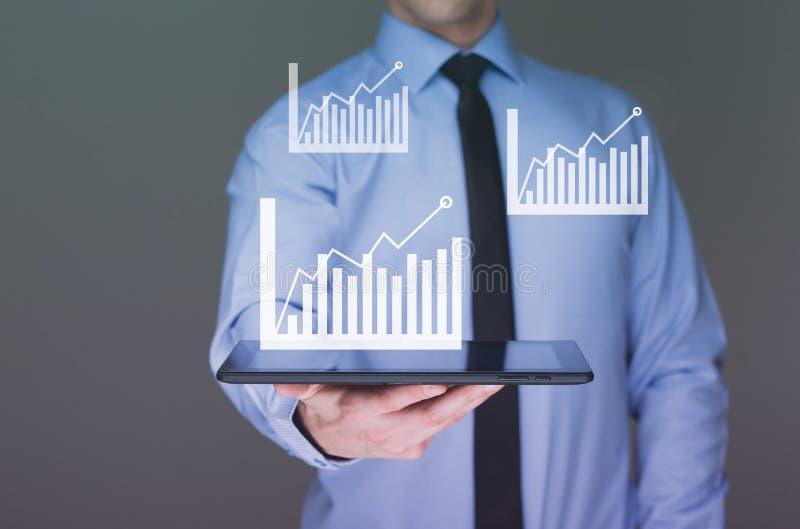 Comprimé de prise d'homme d'affaires avec le graphique sur la technologie de pointe images stock