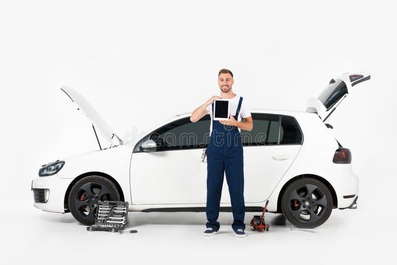 comprimé de sourire d'apparence de mécanicien automobile avec l'écran vide près de la voiture cassée photos stock