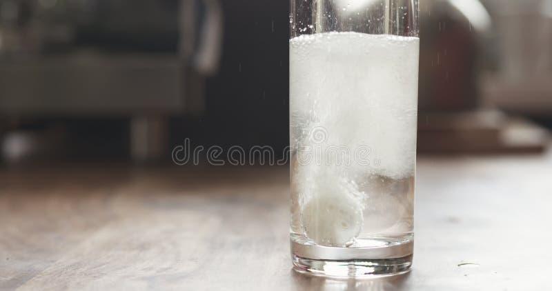 Comprimé effervescent blanc en verre avec de l'eau sur la table photos libres de droits