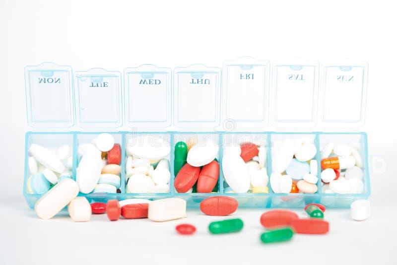 Comprimé et capsule de médecine dans la boîte hebdomadaire de pilule image stock