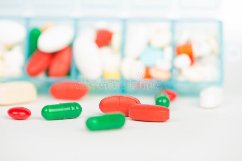 Comprimé et capsule de médecine dans la boîte hebdomadaire de pilule photos stock