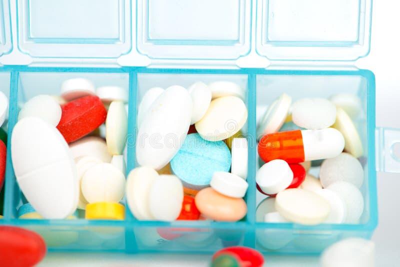Comprimé et capsule de médecine dans la boîte hebdomadaire de pilule photo stock
