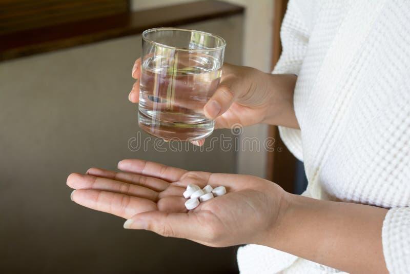 Comprimé et verre femelles de médecine de prise de mains photographie stock