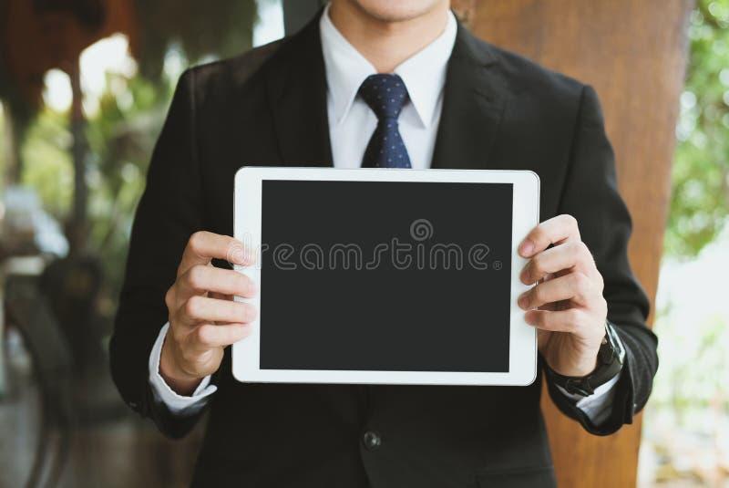 Comprimé numérique de prise d'homme d'affaires sur le lieu de travail expositions de jeune homme dedans photos libres de droits