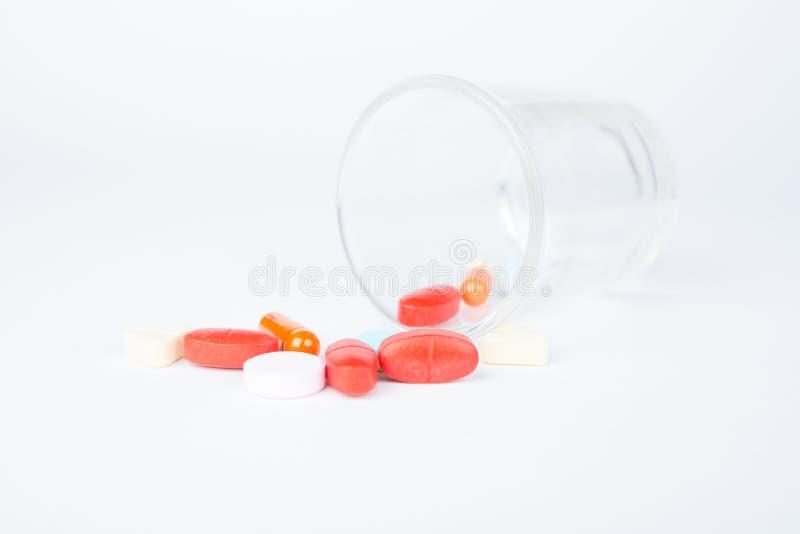 Comprimés et capsule de médecine sur le verre de distribution images stock
